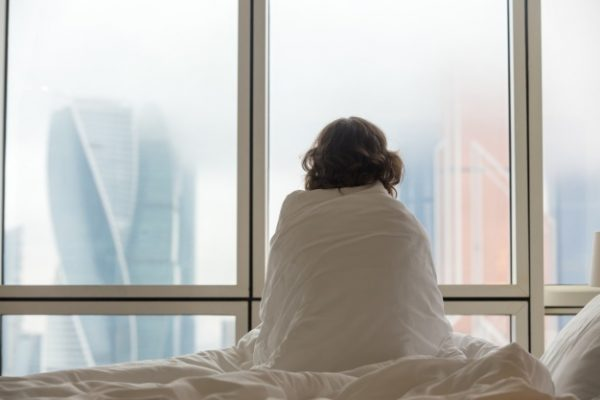 Woman sitting in bed looking through the window | Free Photo